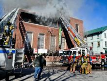Firefighters battle a fire in the Moose Exchange in downtown Bloomsburg on Thursday. (Press Enterprise/Bill Hughes)