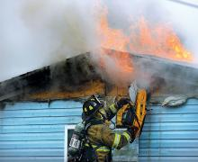 A firefighter uses a saw to open the wall and expose the flames at this home on Tower Driver in Montour Township Friday morning. (Press Enterprise/Keith Haupt)