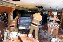 Bloomsburg firefighters work to get to the driver of a pickup truck that crashed through the wall of Pizza Hut and into the dining area Thursday afternoon. (Press Enterprise/Keith Haupt)