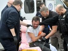 Police officers and EMS workers work together to get Justin Lindsay on a litter while he is secured in a handcuff belt, after he fought with parole officers along First Avenue in Berwick Tuesday afternoon. (Press Enterprise/Jimmy May)