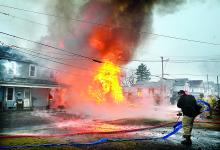 Firefighters set up hoses as the home of Gwen Zubler at 304 East Eighth St. in Bloomsburg collapses in a ball of fire on Tuesday morning. The fire is spreading to the next door home of Larry Poust, at left, at 312 East Eighth Street.