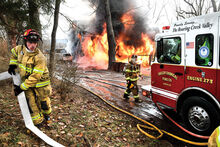 Firefighters lay hose to get water to a fire in Locust Township Friday morning on Mountain Road. (Press Enterprise/Keith Haupt)