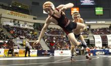 South Side Beaver's Nathan Reckner, foreground, jumps off the mat while trying to escape from the control of Benton's Matt Welliver in a 120-pound second round consolation match Friday morning during the PIAA, Class AA Wrestling Championships in Hershey. (Jimmy May/Press Enterprise photo)