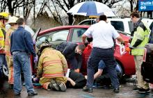 Rescue workers tend to a woman who was caught under her Toyota Prius in the parking lot at Geisinger Medical Center in Danville on Wednesday.  (Press Enterprise/Bill Hughes)