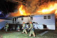 Firefighters work outside a raging fire at 290 W. 11th St., Bloomsburg. (Keith Haupt/Press Enterprise)