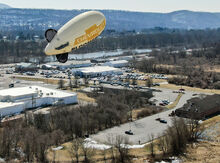 Bloomsburg Chevrolet's advertising blimp stays motionary for a moment, with its line tangled in a tree. Moments later, it broke free and began to head north. The car dealership can be seen in the background of the photo, along Central Road. (Press Enterprise/Jimmy May)