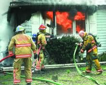 Firefighters pour water on flames as they engulf one of the bedrooms at this home owned by Linda Long along the Susquehanna River in Point Township Wednesday afternoon.