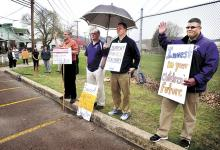 Striking Danville High School teachers picket at the corner of East Market and Wall streets in Danville as the rain begins on Tuesday morning. (Press Enerprise/Bill Hughes)