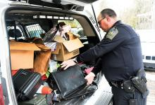 Hemlock Township police officer Harold Morris places evidence in the back of the police vehicle in Fernville Wednesday afternoon. (Press Enterprise/Keith Haupt)