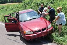Scott Township Sgt. Joe Grassley, left, and officer Vince Taggart, second from right, assist the driver of a Pontiac from her car to her walker after the vehicle went off the side of Neufer Hill Road in Scott Township on Monday afternoon. (Press Enterprise/Jimmy May)