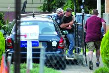 South Centre Township Police Chief Bill Richendrfer tackles Wayne Shiffer as Shiffer tries to go into his home after a two-hour police standoff on the Mifflinville Bridge Monday morning. Shiffer, 47, was first spotted sitting on the ledge of the bridge around 4:17 a.m. He was suicidal, police say.