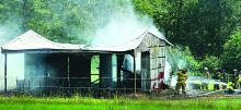 Firefighters work to put out a blaze in a barn filled with hay along Grange Hall Road near Sweet Valley Thursday afternoon.