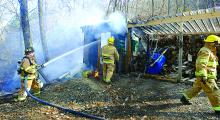 Main Township firefighter Jonathan Broadt, left, douses flames in a small shed near a home in Wonderview, Main Township Saturday afternoon. The shed and woods nearby burned. (Press Enterprise/MJ Mahon)