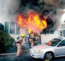 Flames erupt from the front door of 11 Cross St., Danville, Monday afternoon. One man was killed in the blaze, officials say.