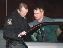Cpl. Greg Fraley escorts David Albertson out of a State Police cruiser at the Bloomsburg barracks Thursday night after police took him into custody at his Fishing Creek Township home. (Press Enterprise/Jimmy May)