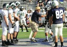 Berwick Football Coach George Curry pushes on the shoulder pads of Marty Grasley while standing on the 50-yard line at the start of an Aug. 23 scrimmage. Someone made an anonymous call to Children and Youth accusing Curry of physically abusing a player based on the photo. The report was ruled unfounded, school officials say.(Press Enterprise file photo/Jimmy May)