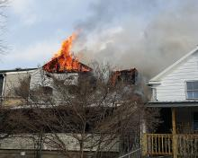 Flames roll out of the attic and roof area of a home on Ash Street in Danville Tuesday afternoon. (Press Enterprise/Chris Krepich)
