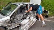 Avery Eddy, 18, Hughesville, reaches inside his mangled car retrieving personal belongings following crash near HRI, Inc. Eddy sustained only minor cuts.(Press Enterprise/Leon Bogdan)