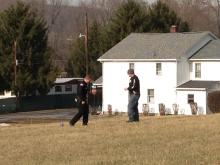 Officers stand near what they say was an actively brewing meth bottle in a field in Catawissa. (Press Enterprise/Kristin Baver)