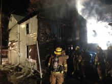 Firefighters work to quench flames at the rear of 311 DL&W Ave. late Tuesday night. (Chris Krepich/Press Enterprise)