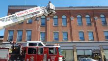 Reliance firefighters Michael Kost, hidden and Jared Coolbaugh, use a ladder truck to check the roof of the Schain building for fire Sunday afternoon.