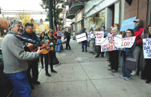 Protestors sing songs outside the Greenly Center along Main Street in Bloomsburg Friday morning. The protestors were on hand as U.S. Congressman Lou Barletta attended a meeting.