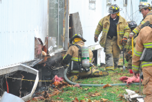 Firefighters work to douse hotspots under a trailer at 6 Rhodes St. in Almedia.