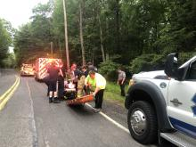 Susan Schwartz/Press Enterprise Rescuers prepare Sandra Koffel to be loaded into a Shickshinny Ambulance after carrying her out of the woods by Shickshinny Falls.