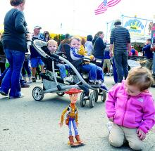 "Paisley Bankus, 2, Berwick, kneels down to get a closer look at a Woody toy, from the ""Toy Story"" movie series, as his bobbles about at the Bloomsburg Fair Sunday. (Press Enterprise/M.J. Mahon)"